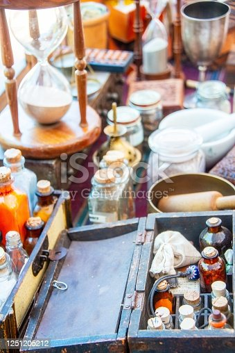 Lot of ancient alchemist instruments, medicine, boxes and bottles over a table