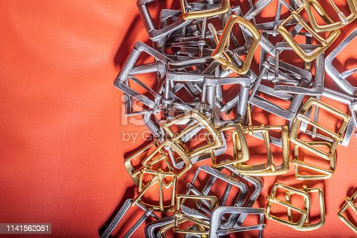 istock A lot of Belt buckles and coral leather background 1141562051