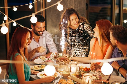 Friends having dinner party at home. Celebrating birthday party for their friend. Thay are happy and well dressed. Home is decorated with festive string lights and candles. Evening or night.