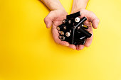 A lot of black aa batteries in male hands on yellow background, view from the top, minimal concept, copy space.