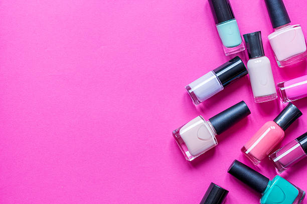 lot of bottles nail polish on pink background top view stock photo