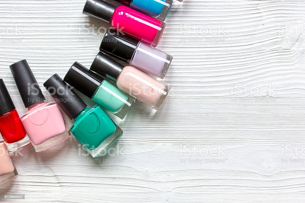 lot of bottles nail polish on wooden background top view stock photo