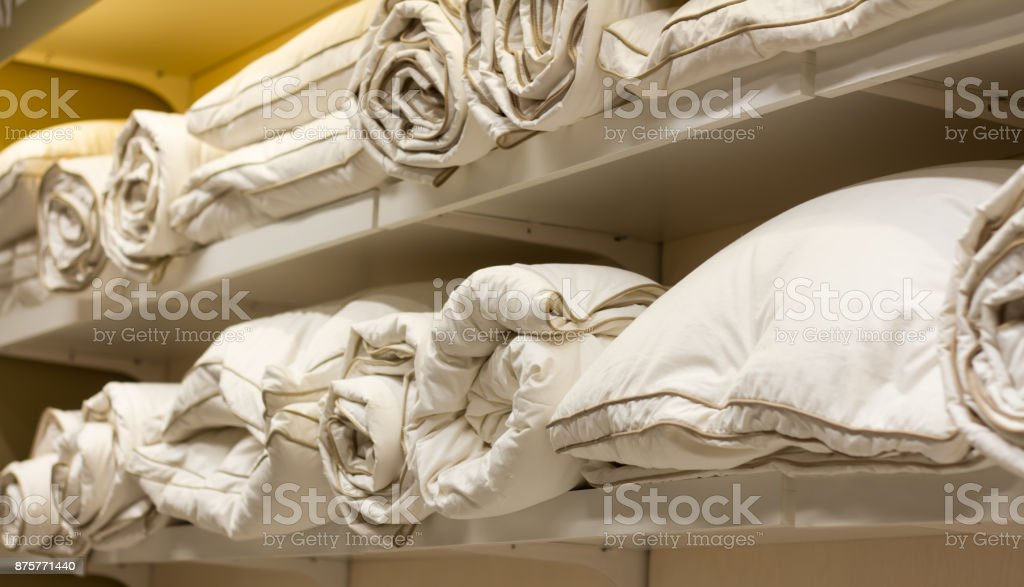 lot of bright pillow and blanket feather lying on the shelf, samples in the store stock photo