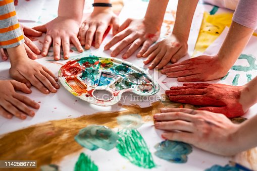 154371635 istock photo A lot of children hands at the table around palette 1142586772