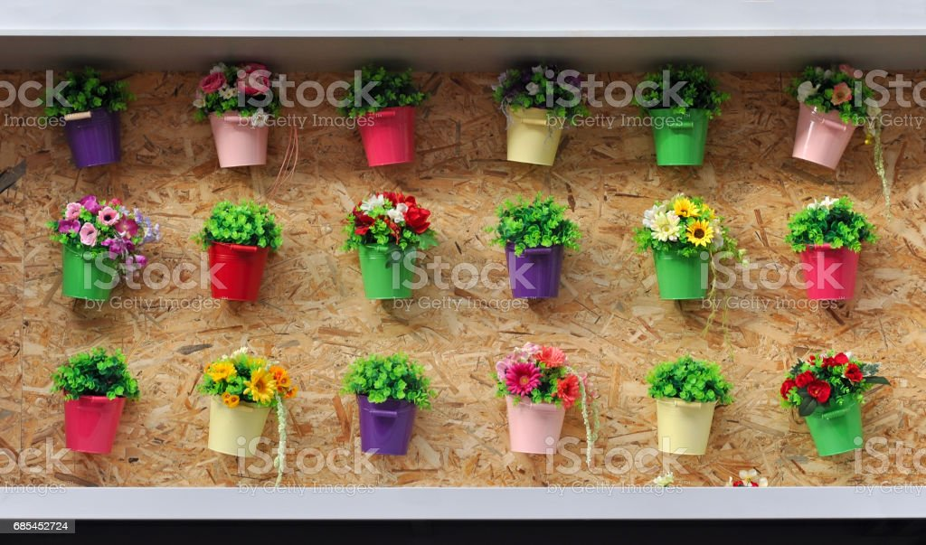 A lot of colored pots with flowers on a cork wall. foto de stock royalty-free