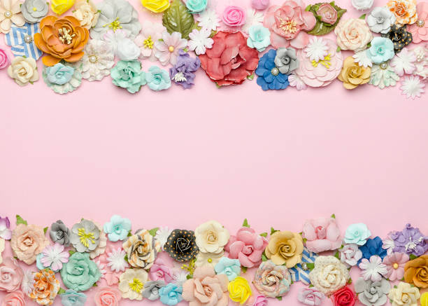 A lot of colorful homemade paper flowers on a pink background