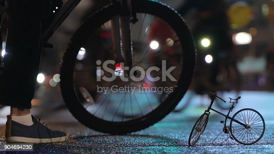 863454090istockphoto Lot of cyclists ride during night cycling bike parade in blur by illuminated night city street against background of small scale model of bicycle. Crowd of people on bike. Bike traffic. Concept sport healthy lifestyle. Bright shining lights. Low angle 904694230