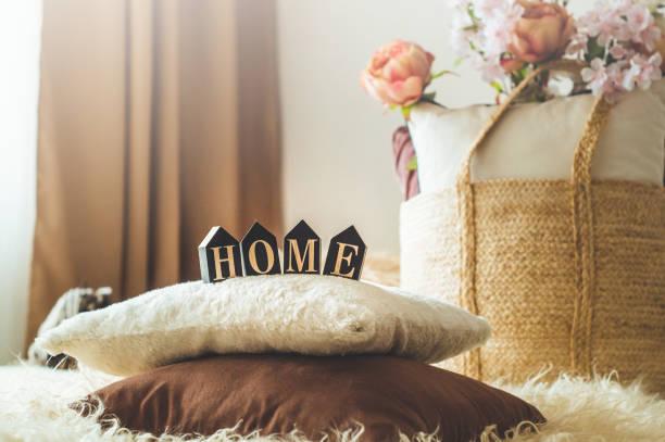 eine menge dekorativer, gemütlicher kissen und die inschrift home - bett landhausstil stock-fotos und bilder