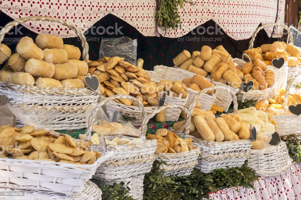 A lot of different smoked homemade cheese in white baskets lies on the wooden counter during the festive street fair stock photo