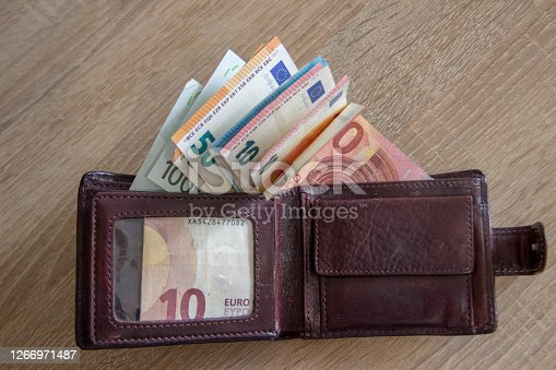 A lot of euro currency lies in a leather wallet. The money is in one compartment of the wallet.