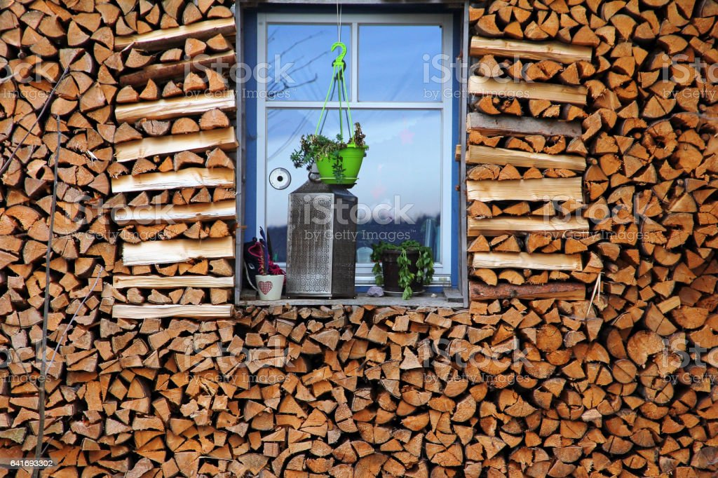A lot of firewood around a window stock photo