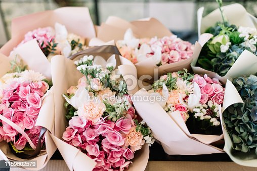 A lot of flower bouquets at the florist shop on the table made of hydrangea, roses, peonies, eustoma in pink and sea green colors