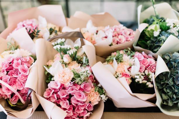veel bloemen boeketten in de bloemist winkel op de tafel gemaakt van hortensia, rozen, pioenen, eustoma in roze en zee groene kleuren - boeket stockfoto's en -beelden