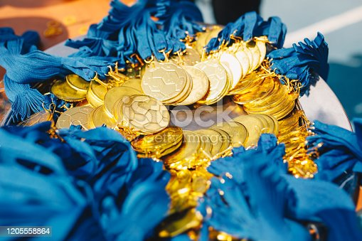 932724052 istock photo A lot of gold medals with ribbons. Golden medals for winners of football soccer competition 1205558864