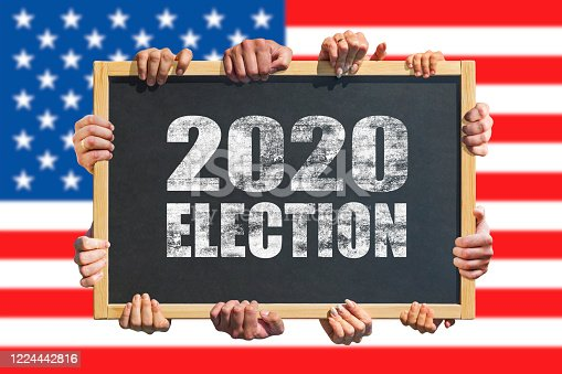 1157022917 istock photo A lot of hands are holding a sign, banner with text 2020 Election on USA flag background. Presidential Election 2020 in United States. Election Day. 1224442816