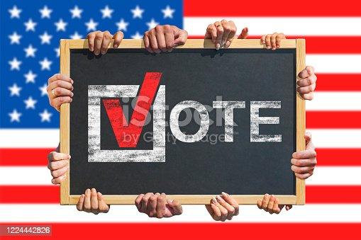 1157022917 istock photo A lot of hands are holding a sign, banner with text VOTE on USA flag background. Election in United States. Election Day. 1224442826