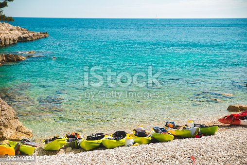 lot of kayaks at rocky beach copy space. summer water activities