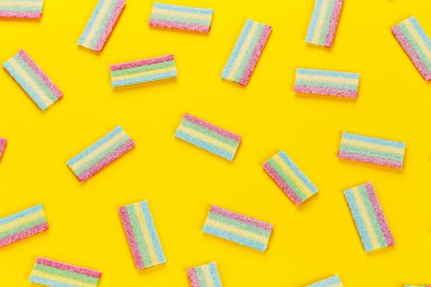 veel multi-gekleurde gelei zoete snoepjes op een gele achtergrond. - kauwgomachtig stockfoto's en -beelden