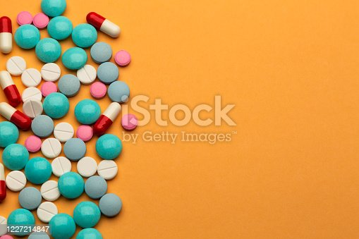 Lot of multicolored pills and tablets on orange background with free space for text or prescription. Concept of drugs addiction.