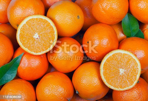 A lot of oranges with some cut in half and leaves.