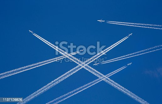 istock A lot of passenger airplanes on the air, busy air traffic, traveling high season starts concept. White planes against blue sky.  Photo manipulation. 1137126826