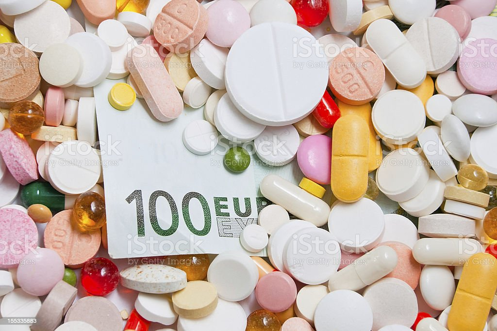 Lot of pills and one hundred euro banknote royalty-free stock photo