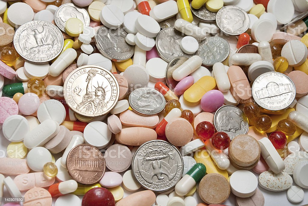 Lot of pills with coins among them royalty-free stock photo
