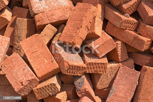 A lot of red bricks are piled up.