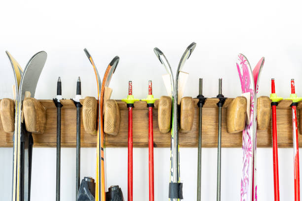 lot of ski hanged on customized wooden wall mount at garage for seasonal storage. extreme winter sport equipment handling at home warehouse - negozio sci foto e immagini stock