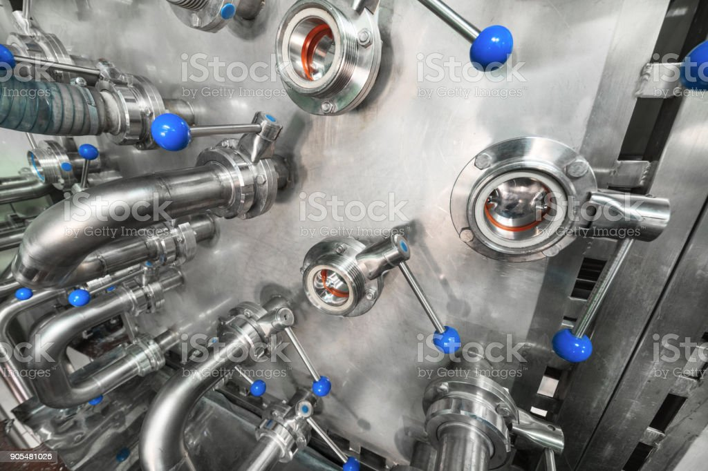 A lot of steel ball valves with blue handles mounted on a metal wall stock photo
