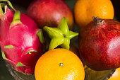 A lot of tropical fruits in a glass vase. Exotic fruits: averrhoa carambola, Pitahaya, Mango, tangerines, pomegranate fruit