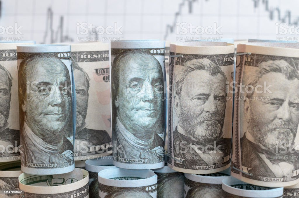 A lot of twisted dollar bills on the background of financial charts. royalty-free stock photo