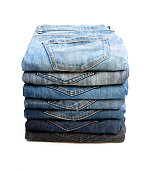 Lot of  used jeans stacked in a pile isolated on white