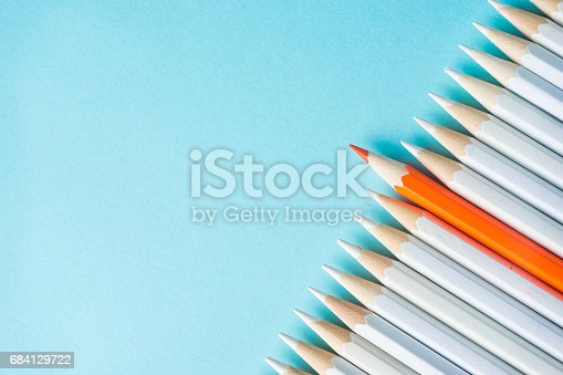 istock lot of white pencils and color pencil on blue paper background. 684129722