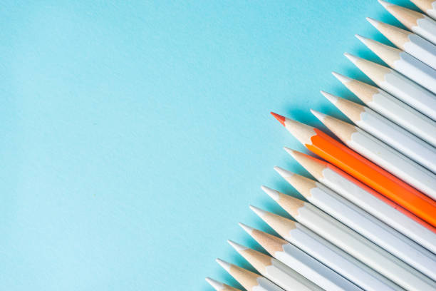 lot of white pencils and color pencil on blue paper background. stock photo
