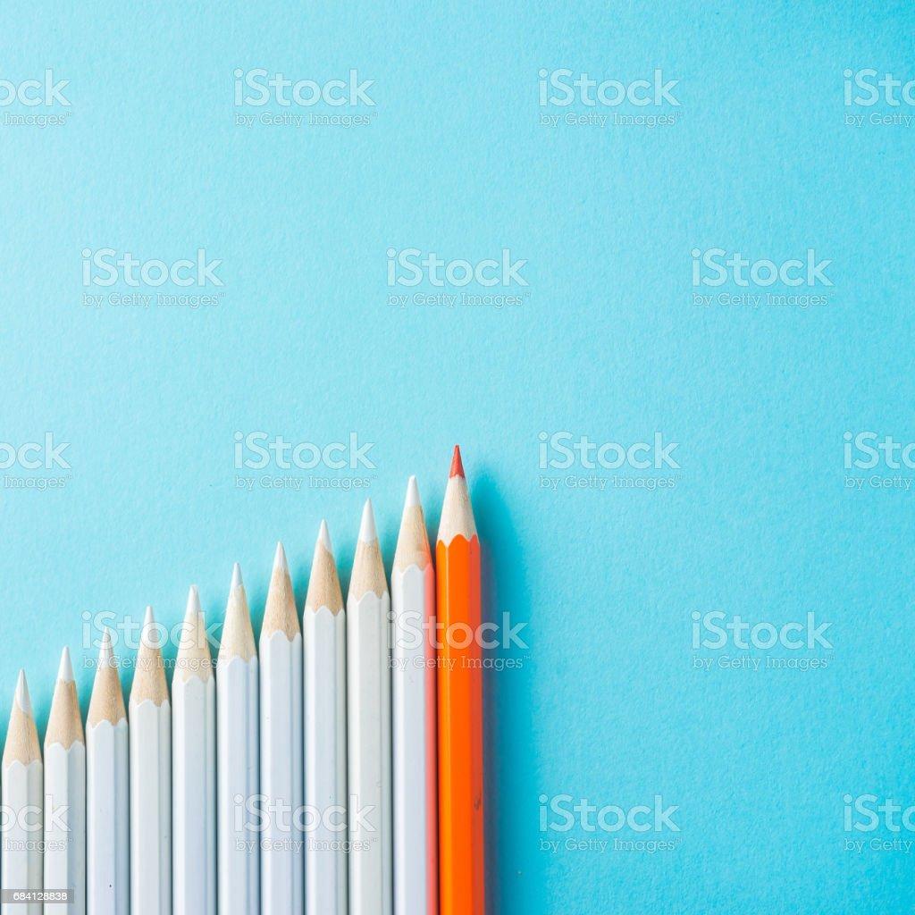 veel witte potloden en één kleur potlood op blauw papier achtergrond royalty free stockfoto