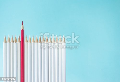 istock lot of white pencils and one color pencil stand on blue paper background 810797982