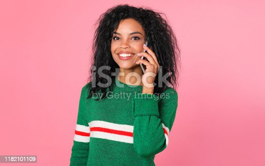 909457386istockphoto A lot to talk about. Busy African American girl in a green sweater with white and red stripes is looking at the camera, smiling broadly while chatting on the phone. 1182101109