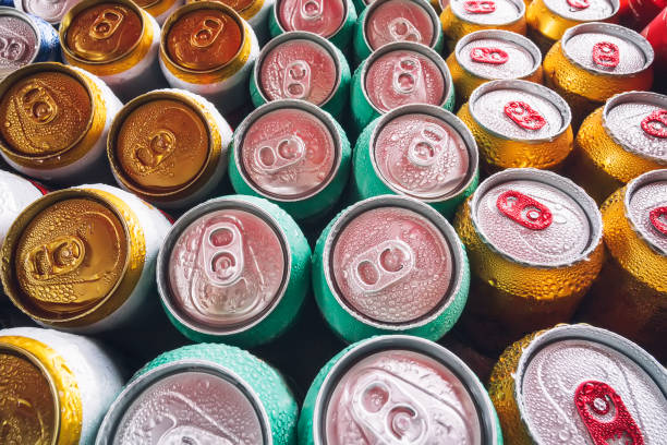 Lots of aluminum cans in the ice in the open fridge. Drops of water on a cold can of drink. Metal cans of beer with ice cubes in mini refrigerator, close up stock photo