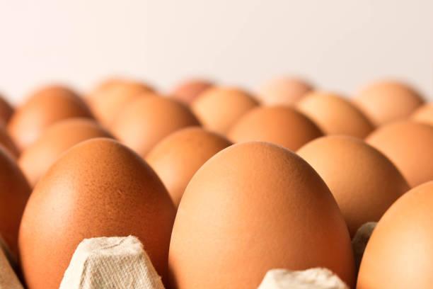 es gibt viele große hühnereier auf hellem hintergrund. hautnah. selektiven fokus - eierverpackung stock-fotos und bilder