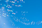 Clear blue sky filled with lot of soap bubbles that travel through the air. Shallow depth of field.
