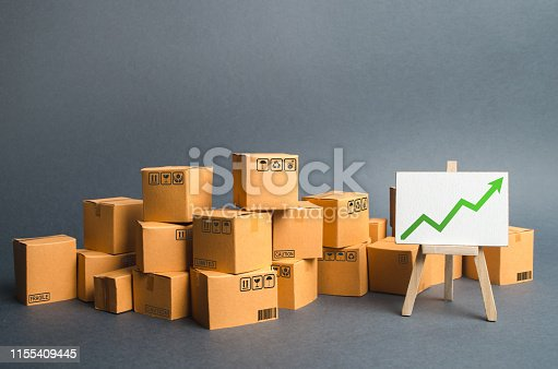 1155852718istockphoto Lots of cardboard boxes and a stand with a green up arrow. rate growth of production of goods and products, increasing economic indicators. Increasing consumer demand, increasing exports or imports. 1155409445
