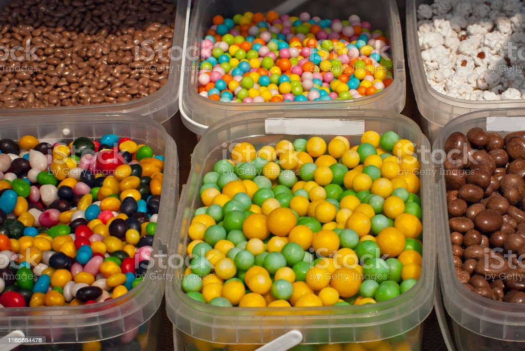 Lots of colorful candies in boxes. Sweets on the table at the fair.