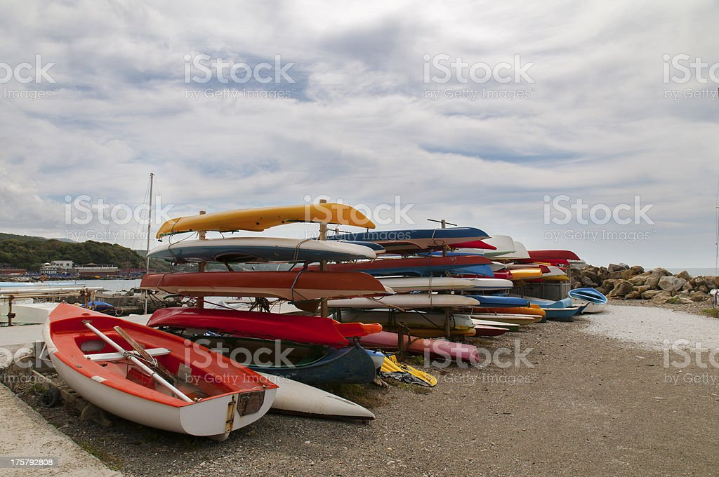 lots of colorful kayaks on beach stock photo