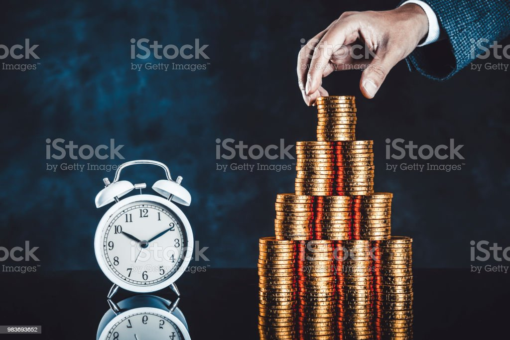 Lots of gold coin and alarm clock stock photo