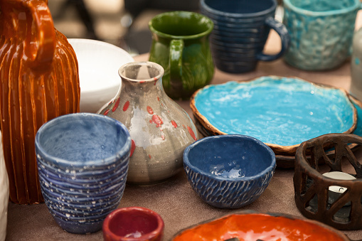 Lots of handmade tableware - ceramic cups, plates at pottery shop