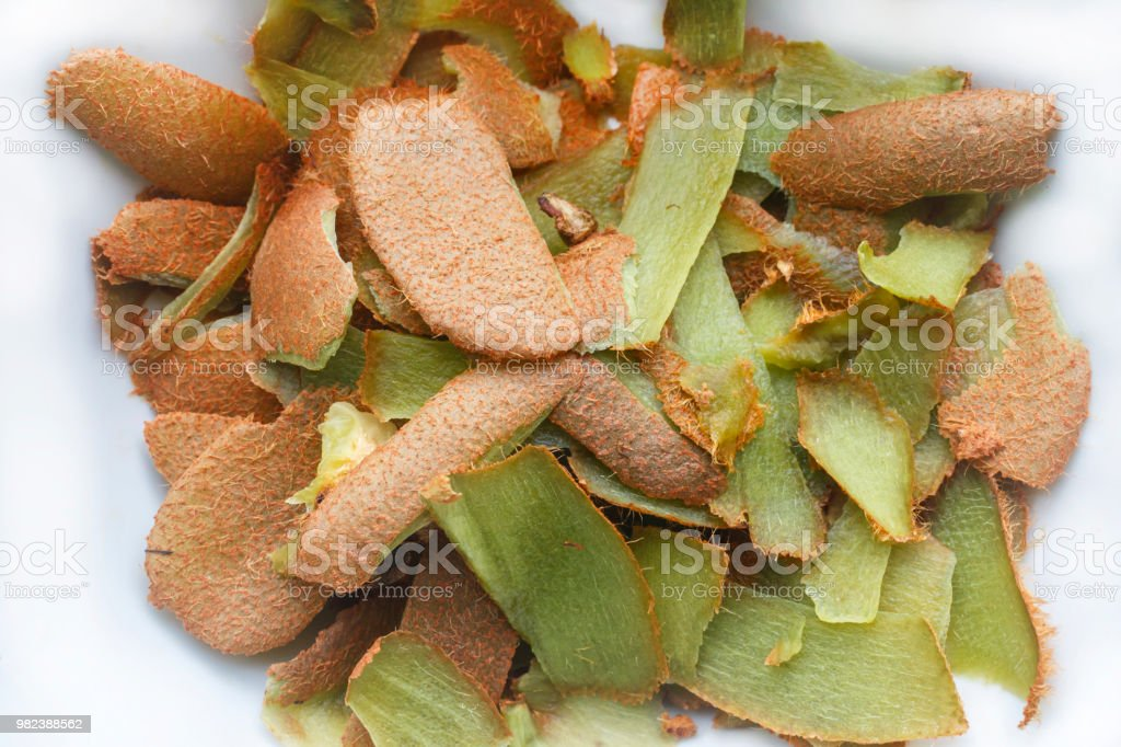 lots of kiwi fruit peels on a white background. Peel of the kiwi background - Foto stock royalty-free di Agrume