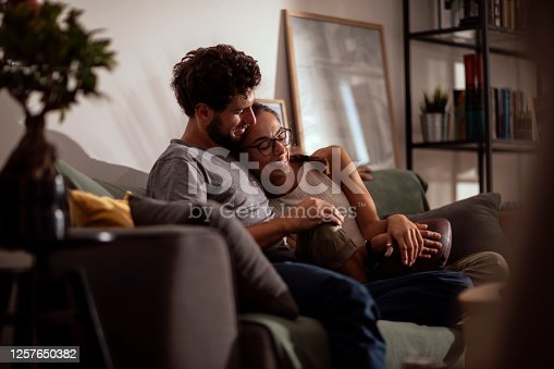 Young loving couple relaxing in their living room, spending time together while sitting on the couch