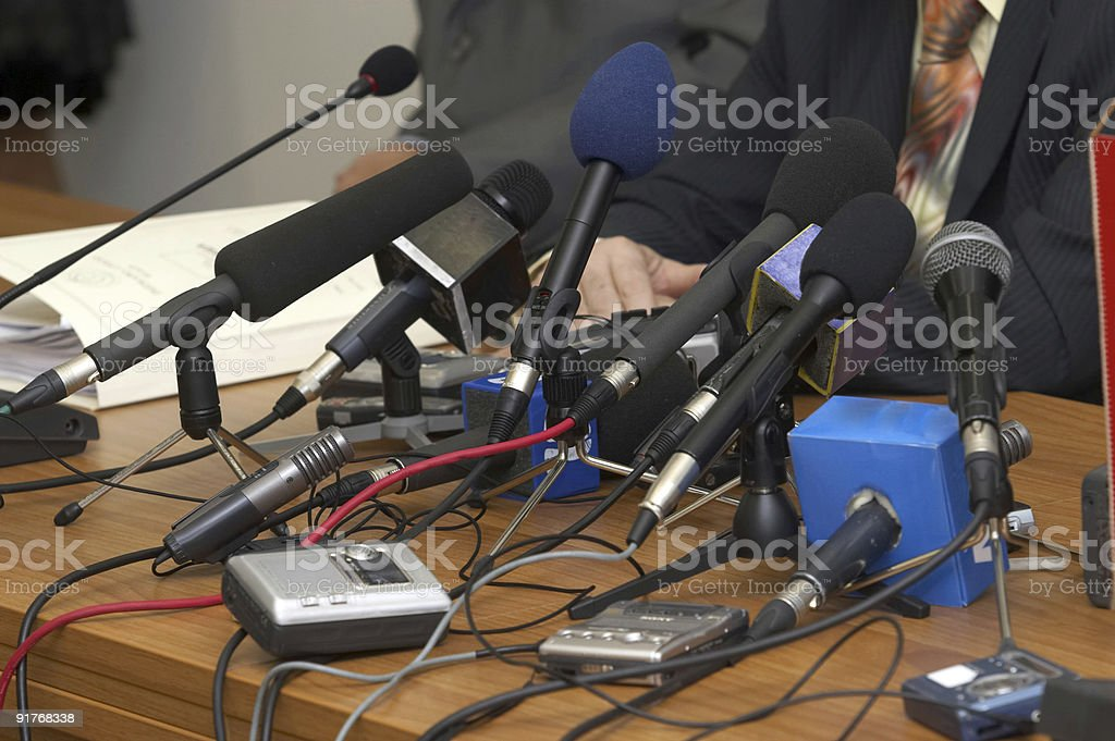 Lots of microphones wired to a podium for a conference royalty-free stock photo