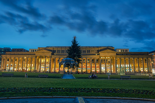 Stuttgart, Germany - November 11, 2019\n\nLots of people around the popular and lively colonnade or arcades of Konigsbau at Christmas at night time. Capture taken from the Schlossplatz (castle square)